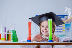 Smiling little chemist posing with colorful flasks. Portrait of smiling little chemist posing with colorful flasks stock photo