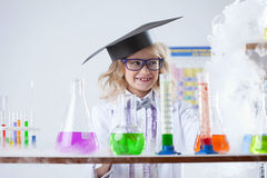 Smiling little chemist puts experiments in lab Royalty Free Stock Photos