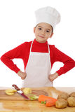 Smiling little chief-cooker on the desk Stock Image