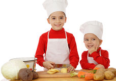 Smiling little chief-cookers on the desk Stock Photos