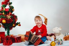 Smiling little child in a Christmas costume with an accordion in his hands sitting under the Christmas tree royalty free stock images