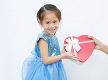 Smiling little child girl receiving red heart gift box isolated on white background. Concept Valentine`s Day stock image