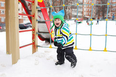 Smiling little child on playground in winter Stock Images