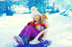 Smiling little child sitting on sled in winter. Day Royalty Free Stock Photos