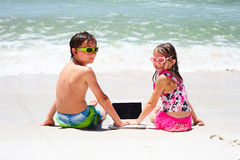 Smiling little children with laptop on beach Royalty Free Stock Photography