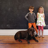 Smiling little children with their dog at home Stock Image