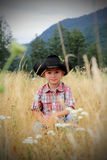 Smiling Little Cowboy. A smiling little cowboy with a black hat and plaid shirt sitting in the tall grass and wild flowers with mountains in the background Royalty Free Stock Photo