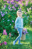 Smiling little cute blonde child girl 4-9 years with a bouquet of lilac in the hands in jeans and shirt Stock Photos