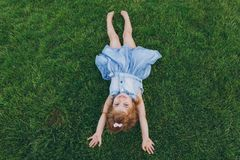Smiling little cute child baby girl in denim dress lie on green grass lawn, raise hands up in park. Mother, little kid. Daughter. Mother`s Day, love family royalty free stock photo