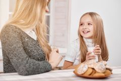 Smiling little daughter sits kepping milk glass near mother. royalty free stock photo