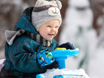 Smiling little driver holds steering wheel of his toy car. In winter Stock Photography