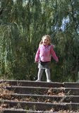 Smiling little girl. Adorable blond girl shout for joy. Little  girl wears autumn clothes. 4 years old girl is going to walk down a stairs Royalty Free Stock Photo