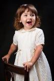 Smiling little girl. Over dark background Stock Photo