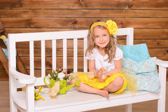 Smiling little girl and alive chickens on bench Royalty Free Stock Image