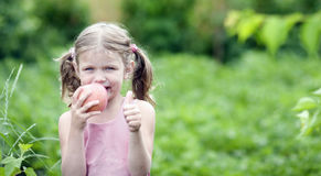 Smiling Little girl with a Apple. Royalty Free Stock Image