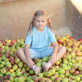 Smiling little girl on apples Stock Photography