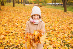 Smiling little girl with autumn leaves in park Stock Photos