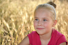 Smiling little girl on a background of gold grass. Smiling little girl sitting on a background of gold grass Royalty Free Stock Photo