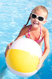 Smiling little girl with ball in swimming pool Royalty Free Stock Photography