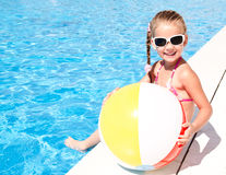 Smiling little girl with ball in swimming pool Stock Image