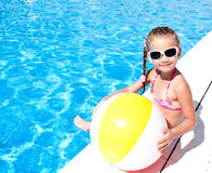 Smiling little girl with ball in swimming pool Stock Images