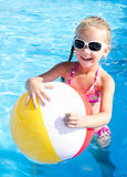 Smiling little girl with ball in swimming pool Stock Photo