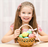 Smiling little girl with basket full of colorful easter eggs Stock Photos