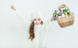 Smiling little girl with basket full of colorful easter eggs Stock Photo