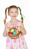 Smiling little girl with basket full of colorful easter eggs iso Stock Images