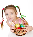 Smiling little girl with basket full of colorful easter eggs iso Royalty Free Stock Photography