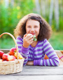 Smiling little girl with basket of red apples Royalty Free Stock Images