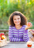 Smiling little girl with basket of red apples Stock Photo