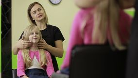Female hairdresser asking girl how to cut hair in salon stock footage