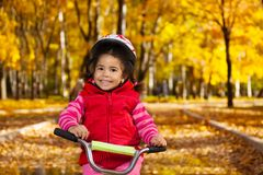 Smiling little girl on a bicycle Stock Images