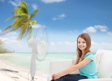 Smiling little girl with big fan at home Stock Image