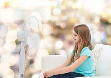 Smiling little girl with big fan at home Stock Images