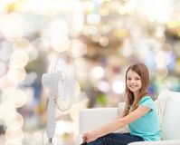 Smiling little girl with big fan at home Stock Photos