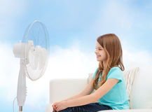 Smiling little girl with big fan at home Royalty Free Stock Photo