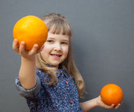 Smiling little girl with big orange. Grey backgriund Royalty Free Stock Image