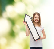 Smiling little girl with blank arrow pointing up Stock Photos
