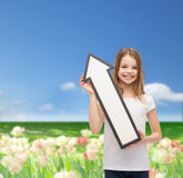 Smiling little girl with blank arrow pointing up Royalty Free Stock Photography
