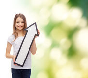 Smiling little girl with blank arrow pointing up Royalty Free Stock Images