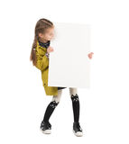 Smiling little girl with blank sheet in hands Royalty Free Stock Image