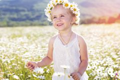 Smiling little girl with bouquet of chamomiles Stock Photos