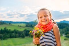 Smiling little girl with a bouquet of wild flowers on a background of a mountain landscape royalty free stock photos