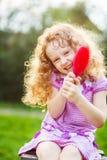 Smiling little girl brushing her hair. Stock Images