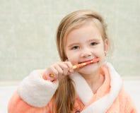 Smiling little girl brushing teeth in bath Royalty Free Stock Photos