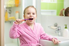 Smiling little girl brushing teeth in bathroom royalty free stock photography