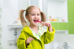 Smiling little girl brushing teeth in bathroom royalty free stock image