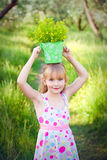 Smiling little girl with a bucket of flowers on her head  Royalty Free Stock Photos